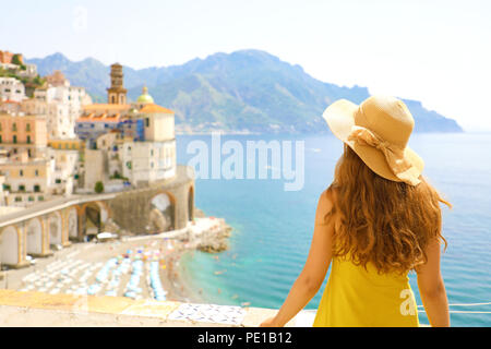Summer holiday in Italy. Back view of young woman with straw hat and yellow dress with Atrani village on the background, Amalfi Coast, Italy - Stock Photo