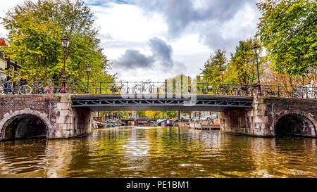 View of a bridge over the Brouwersgracht (Brewers Canal) from a canal tour boat in the Herengracht in the historic city center of Amsterdam, Holland - Stock Photo