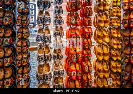 Typical painted wooden shoes in a Dutch souvenir shop in the old city center of Amsterdam, the Netherlands - Stock Photo