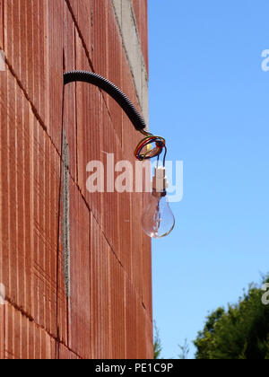 Single light bulb hanging from a wire on the exterior of a newly built wall at a house in Cessenon-sur-Orb, France - Stock Photo