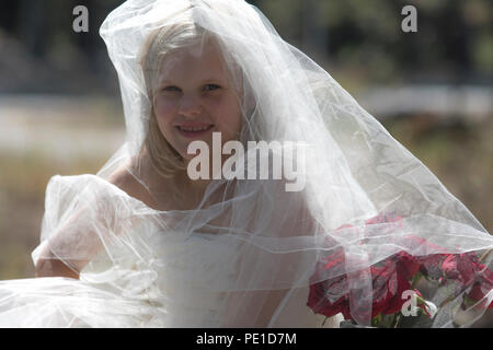 Fantasy, 8-9 year attractie blonde, wearing aunt's wedding dress & veil. Sitting outdoors on large rock beside vase of red roses. - Stock Photo