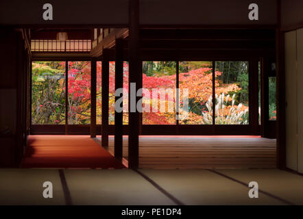 Traditional Japanese room interior with a beautiful colorful autumn nature scenery behind the windows. Tenjuan historic temple hall, Nanzen-ji complex - Stock Photo