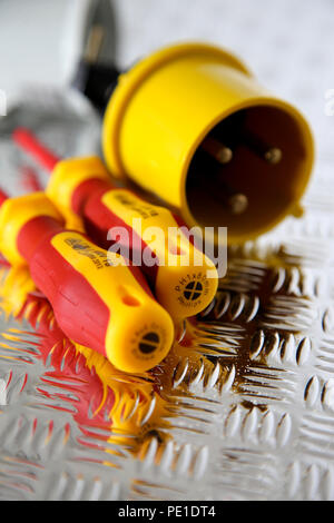 Electric screwdrivers with an industrial electric plug on a steel chequer tread plate - Stock Photo