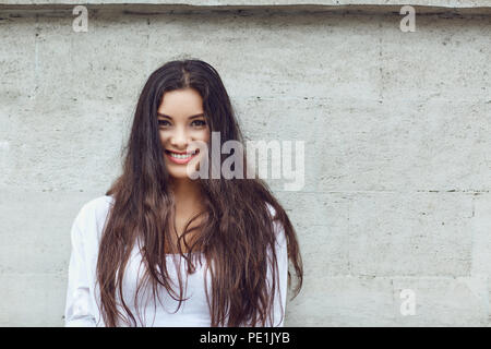 The brunette girl on a gray wall background.  - Stock Photo