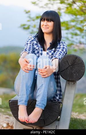 Teen girl barefeet barefoot bare feet foot bare legs smiling shy sitting on wooden bench wearing Blue denim denims pants plaid shirt full length body - Stock Photo