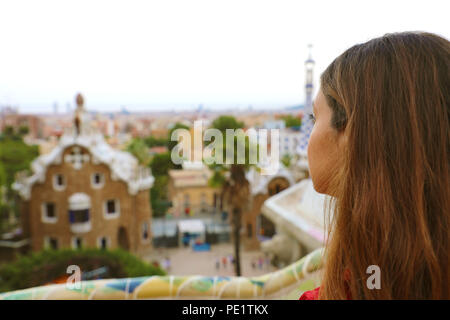 Back view of woman in Park Guell admiring landscape from terrace of the park, Barcelona, Spain - Stock Photo