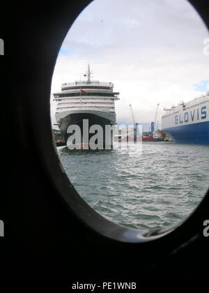 A view of the Cunard cruise liner, Queen Victoria, framed by the porthole on the SS Shieldhall, Britain's largest working steamship. - Stock Photo