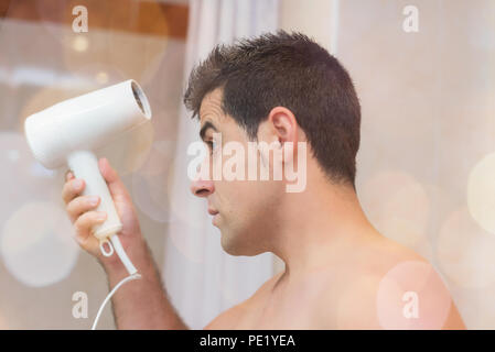 Handsome man drying his hair with a hair dryer. Concept beauty and care of man - Stock Photo