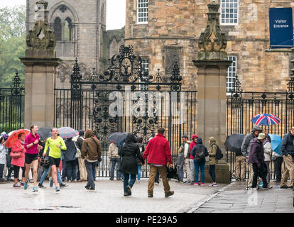 Holyrood, Edinburgh, Scotland, United Kingdom, 12th August 2018. UK Weather: the rain and mist as the remnants of Storm Debby hits the capital does not deter tourists at Holyrood Palace in front of the large ornate gate. People queuing to enter the palace holding umbrellas and two women jogging - Stock Photo