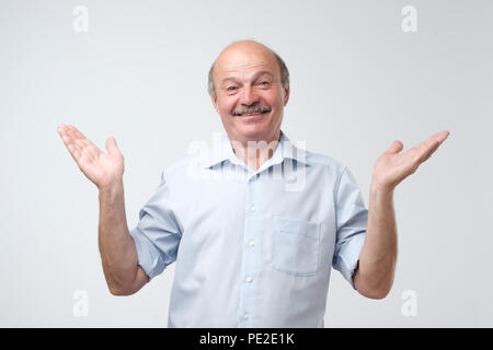 Indoor portrait of confused senior man in blue shirt showing I have no idea gesture, shrugging shoulders and raising hands, standing against gray back - Stock Photo