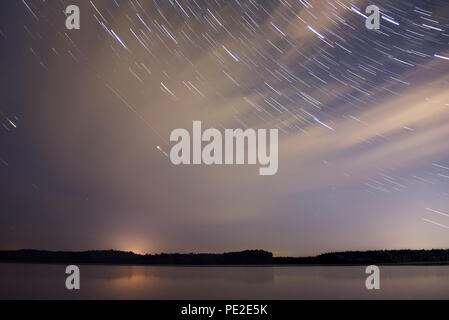 Amazing night landscape with a forest reflected in the smooth water of the river, clouds and stars in the form of tracks on a dark blue sky - Stock Photo