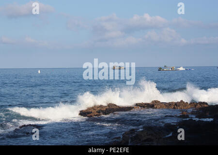 Waves crashing into volcanic rock along the shore of the Pacific Ocean in the Kona District, with boats in the background, Hawaii, USA - Stock Photo