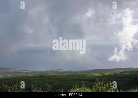 The rolling hills of pastureland in North Kohala, Hawaii, with low lying rainclouds casting shadows over the land and the Pacific Ocean in the backgro - Stock Photo