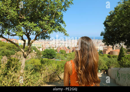 Back view of attractive woman looking at Barcelona cityscape from Bunker del Carmel viewpoint - Stock Photo