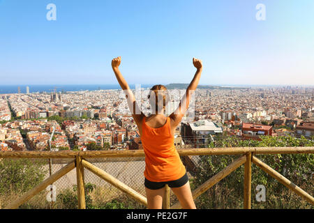 Winner fitness woman comes to the top of Barcelona and enjoying cityscape from belvedere. Excited attractive young woman in sportswear cheerful - Stock Photo