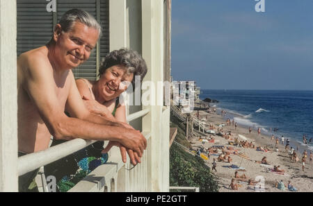 A smiling elderly American couple in their bathing suits relax on the sunny porch of their summer rental apartment that gives them a bird's-eye view of sunbathers and strollers on sandy Laguna Beach along the blue Pacific Ocean in Southern California, USA. Model Released. - Stock Photo
