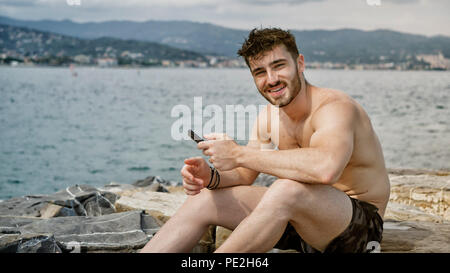 Young man at beach listening to music with earphones - Stock Photo