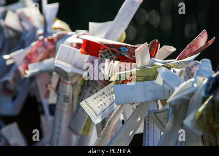 Omikuji (fortune-telling paper strip) tied to a rope at a Japanese temple in Nikko, Japan. - Stock Photo