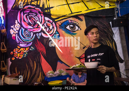 Young man carrying his lunch at the Bến Thanh Street Food Market, Ho Chi Minh City, Vietnam - Stock Photo