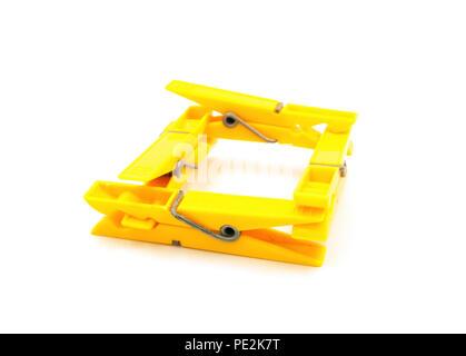 Four yellow pegs on white background - square - Stock Photo