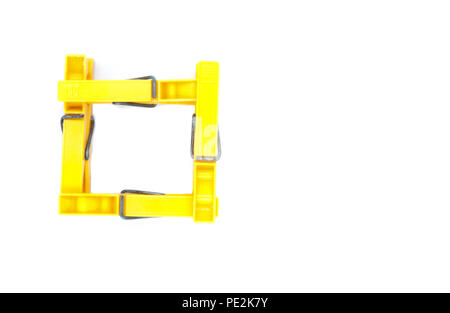 Four yellow pegs on white background - square from top - Stock Photo