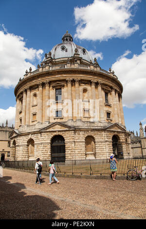 Woman standing looking at the The Radcliffe Camera part of the Bodleian Library situated in Radcliffe square Oxford England UK - Stock Photo
