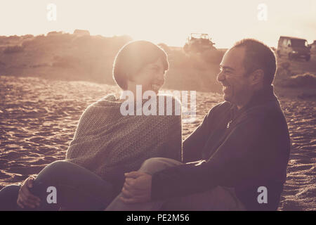 nice beautiful middle age 40 years old couple man and woman caucasian hugged and stay together on the beach sitting in the sand and enjoying a golde a - Stock Photo