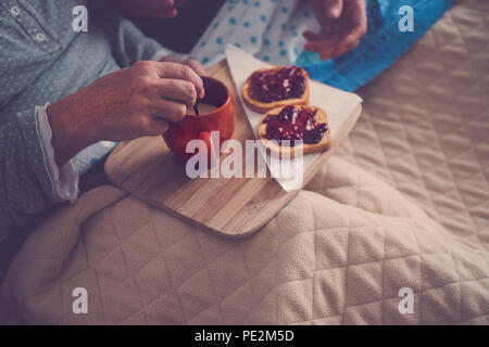 caucasian aged couple doing breakfast at home in the bed. nice natural scene at home for togheterness life concept. love and carefree people married. - Stock Photo