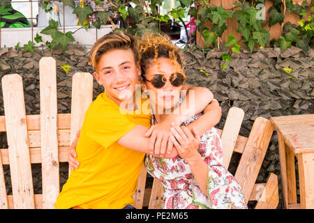 mother and son hugging with smile and enjoy leisure time together with love. family teenager boy 14 years old and mom 43 have fun sitting on a wodd be - Stock Photo