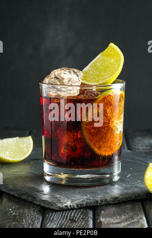 Rum and cola cocktail on dark background - Stock Photo