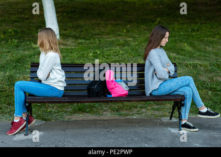 Two girls schoolgirl quarreled in the summer in the park. They sit on a bench. The concept of conflict, scandal, problems in the family, discontent. E - Stock Photo