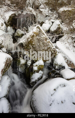 Stream cascading down the side of the Zezere Glacial Valley in winter, creating freezing icicles over the boulders among the snow covered rocks, Serra - Stock Photo