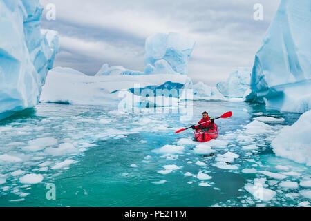 extreme tourism, winter kayaking in Antarctica, adventurous man paddling on sea kayak between icebergs - Stock Photo