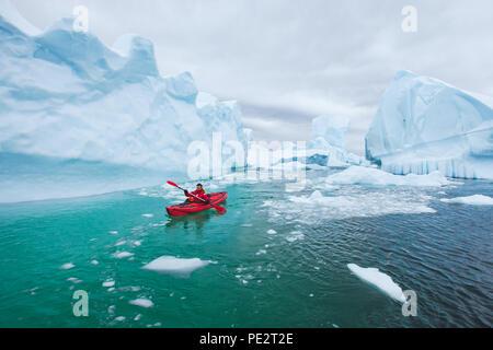 man paddling on kayak between ice in Antractica in Iceberg Graveyard, extreme winter kayaking, polar adventure near Pleneau island - Stock Photo