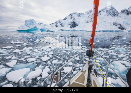 sailing boat in Antarctica, yacht navigation through icebergs and sea ice - Stock Photo
