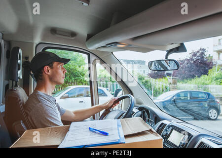 delivery transportation service job, driver man with package box driving truck car vehicle - Stock Photo