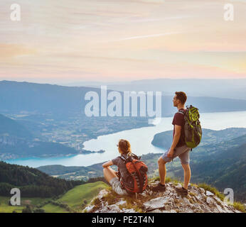 couple of hikers relaxing on top of mountain with beautiful panoramic view outdoors, two tourists backpackers during hike, adventure honeymoon - Stock Photo