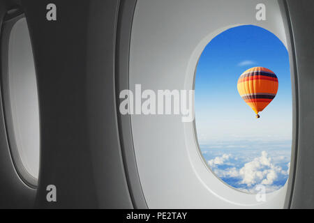 dream travel, hot air balloon flying in sky  seen from window of airplane, surprise concept - Stock Photo