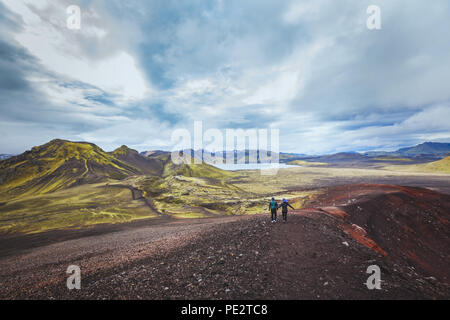 hiking in Iceland near Landmannalaugar, couple of backpackers walking in beautiful moon landscape, travel - Stock Photo