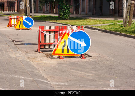 road sign narrowing the road, detour in the city on sunny summer day - Stock Photo