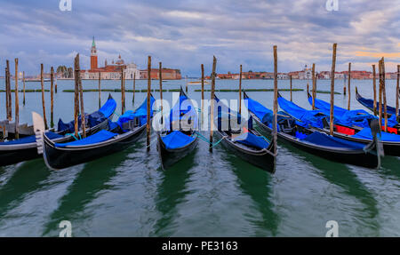 Gondolas along the picturesque Grand Canal at Piazza St Marco or Saint Mark's square at sunrise with the San Giorgio Maggiore church in the background - Stock Photo