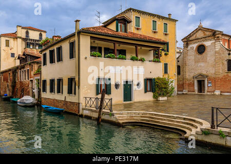 Venice, Italy - September 23, 2017: Typical view of a weathered building facade on a picturesque canal in Venice, Italy - Stock Photo
