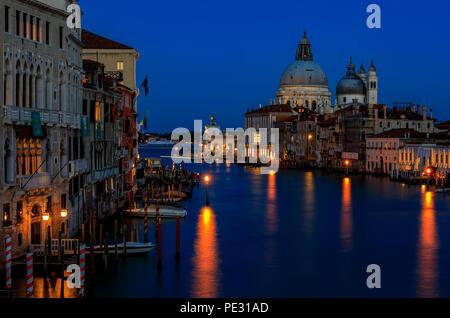 Sunset at the iconic 17th-century Santa Maria di Salute Basilica, view from Academia bridge or Puente de la academia along the Grand Canal in Venice,  - Stock Photo