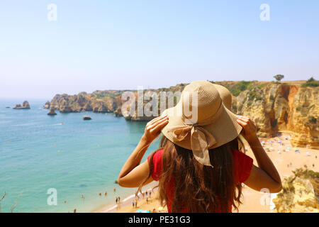 Woman with hat facing stunning view at Lagos beach in Southern Portugal - Stock Photo