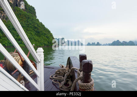 View of Halong Bay, North Vietnam, from the bow of a boat with handrail on the left. - Stock Photo