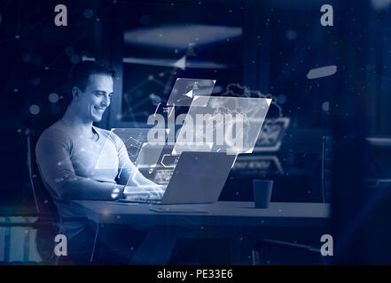 Young man working on laptop at night in dark office. The designer works in the later time. - Stock Photo