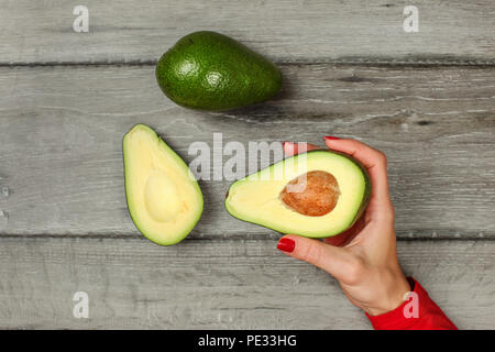Tabletop view, woman hand holding avocado cut in half with whole pear above. - Stock Photo