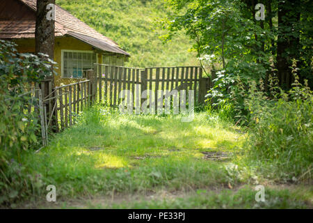 Old wooden rural house in a mountainous area in the Carpathians. Traditional building. Yard with green grass. - Stock Photo