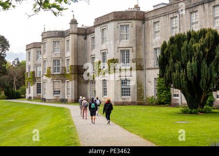 UK, Wales, Anglesey, Llanfairpwllgwyngyll, Plas Newydd House, visitors on path beside Menai Straits - Stock Photo