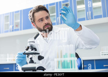 New cure. Professional genius bearded biologist holding a pill and looking at it while developing new cure - Stock Photo